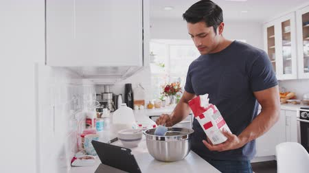 mistura : Millennial man preparing cake mix following a recipe on a tablet computer, adding flour, close up Stock Footage