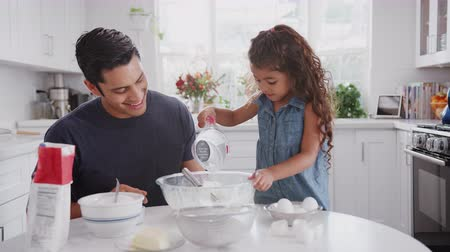 tojás : Jump cut clip of father and young daughter preparing cake mix in their kitchen, close up