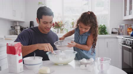 aydınlatmalı : Hispanic father and his young daughter preparing cake mix in their kitchen, close up Stok Video