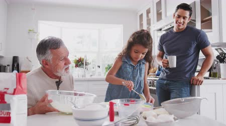 otcovství : Young Hispanic girl baking with grandfather and father in the kitchen filling cake forms, close up