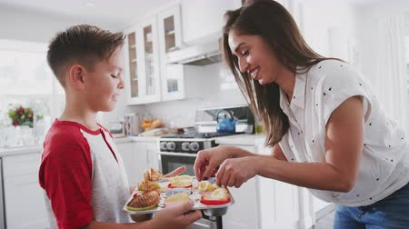 pre hispanic : Pre-teen Hispanic boy presenting the cakes he has baked to his proud mother, close up, side view Stock Footage