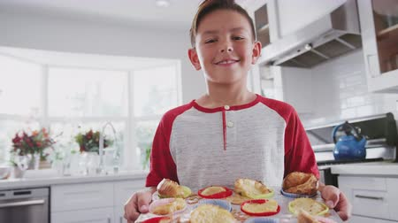 pré adolescente : Proud pre-teen Hispanic boy standing in kitchen presenting the cakes he's made to camera, close up