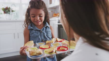 гордый : Happy young girl walks into focus and presents the cakes she's made to her mum, over shoulder view Стоковые видеозаписи