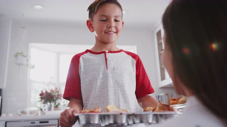 orgulho : Pre-teen boy walks into focus and presents the cakes he's made to his mum, over shoulder view