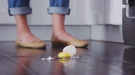 tojás : An egg falling to the kitchen floor and breaking on the wooden floorboards, low angle, slow motion