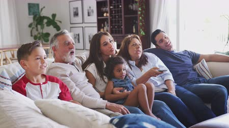 elliler : Three generation Hispanic family sitting on the sofa watching TV, grandmother using remote control