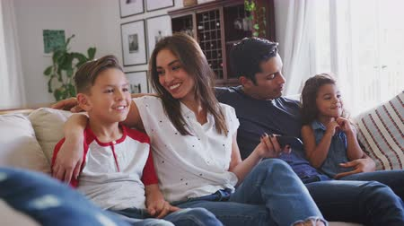 сестры : Young Hispanic family sitting on the sofa at home watching TV together, close up Стоковые видеозаписи