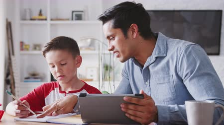 kısa : Hispanic pre-teen boy sitting at dining table working with his home school tutor, close up