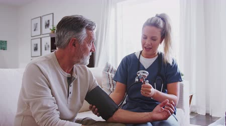 sphygmomanometer : Female healthcare worker taking the blood pressure of a senior man during a home health visit