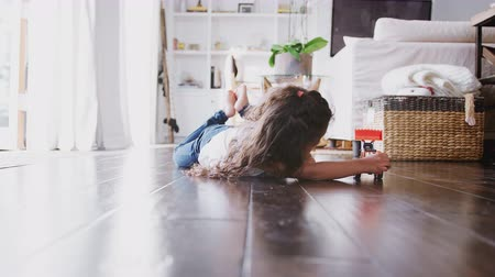 teljes hosszúságú : Young Hispanic girl lying on the floor in the sitting room playing with toy digger truck, front view