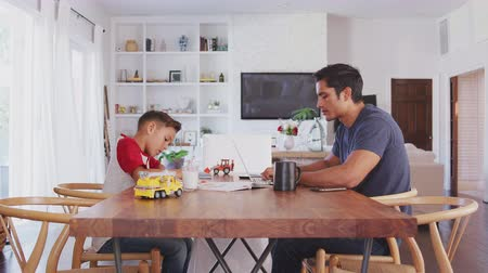 kısa : Hispanic father and son working opposite each other at the dining room table, side view, close up