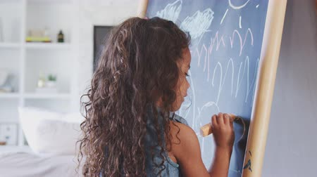 tablica : Young Hispanic girl drawing with chalks at a blackboard at home, close up, back view Wideo