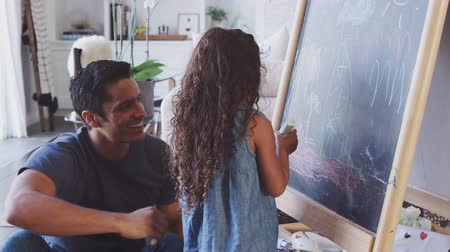 tablica : Father sitting on the floor at home drawing on a blackboard with his young daughter, close up