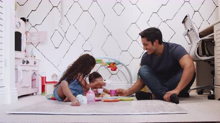 cross legged : Young girl playing tea party sitting on the floor with dad, and baby brother beside them