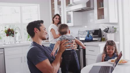 orgulho : Young Hispanic family in their kitchen, mum cooking at hob, dad lifting baby in the air, close up