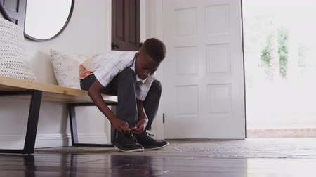 cadarço : Low angle view pre-teen black boy tying his shoes before leaving home, close up