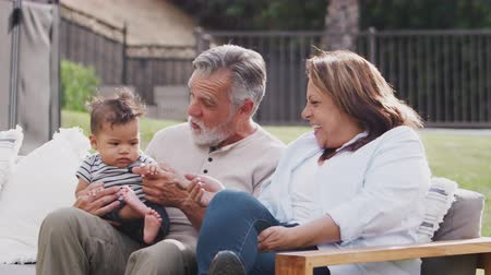 elliler : Senior Hispanic couple sitting on a seat in the garden with their baby grandson, close up