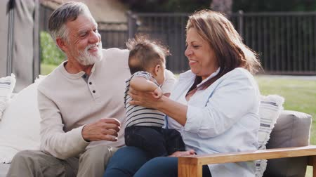 dospělí : Senior Hispanic couple sitting on a seat in the garden passing their baby grandson over, close up
