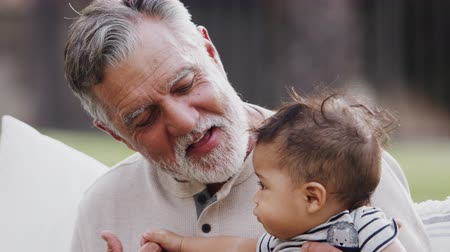 atenção : Senior Hispanic man sitting in the garden with his baby grandson on his knee, talking to him, head and shoulders close up
