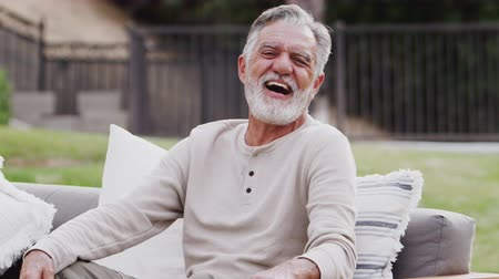 slapping : Senior Hispanic man sitting on a sofa in the garden laughing to camera, waist up, close up