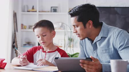 rövid : Pre-teen Hispanic boy sitting at the dining table working with his home tutor, close up