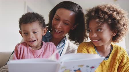 él : African American mum sitting on sofa reading to her two kids, low angle, close up