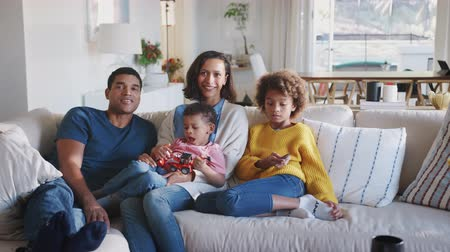 pré adolescente : Young African American family relaxing on sofa watching TV together at home