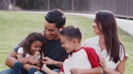 etnisite : Happy young Hispanic family sitting on grass in the park tickling each other and smiling to camera Stok Video