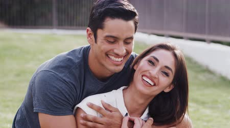 each other : Millennial Hispanic couple embracing in the park and smiling to camera, close up Stock Footage