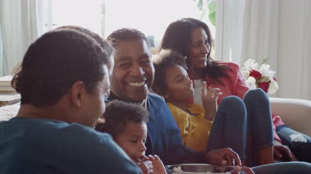 elliler : Three generation African American family sitting on sofa watching TV and eating popcorn together, close up