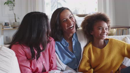 elliler : Three generation female family group sitting on a sofa watching TV laughing together, close up Stok Video