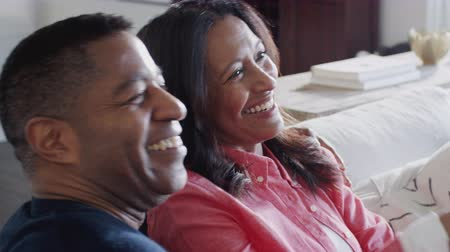 elliler : Happy middle aged African American couple sitting together on the sofa watching TV, close up, elevated view