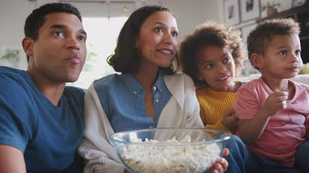 попкорн : Young African American family sitting on the sofa watching TV and eating popcorn, low angle, close up Стоковые видеозаписи