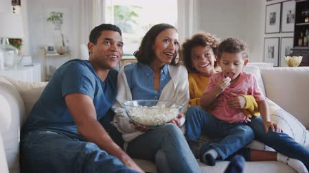 попкорн : Young African American family sitting on the sofa at home watching TV and eating popcorn