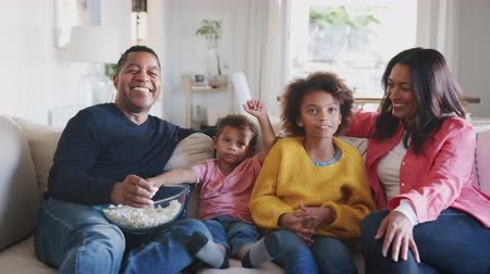 elliler : Two kids and their grandparents sitting on sofa watching TV, eating popcorn and laughing, close up