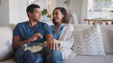 попкорн : Young adult African American couple on the sofa in their living room talking, laughing and eating popcorn