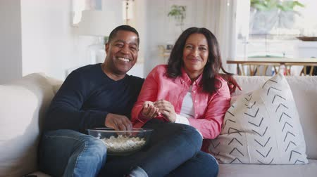 elliler : Happy African American couple reclining on sofa, watching TV and eating popcorn, close up