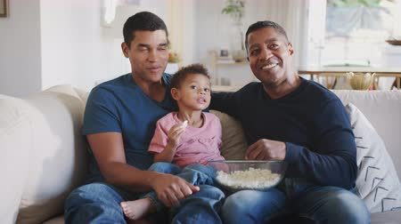 попкорн : Three generation male family group sitting on a sofa eating popcorn and watching TV together