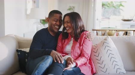 elliler : Middle aged African American couple embracing on the sofa in their living room laughing, close up