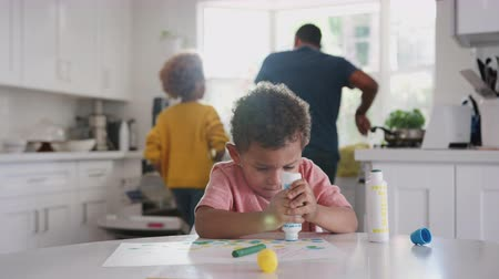 focus on foreground : Young African American boy painting a picture in kitchen while father and sister prepare food in the background Stock Footage