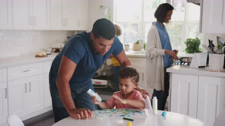 alimentacion bebe : Dad watches son painting in kitchen, returns to chores with mother and daughter in the background Archivo de Video