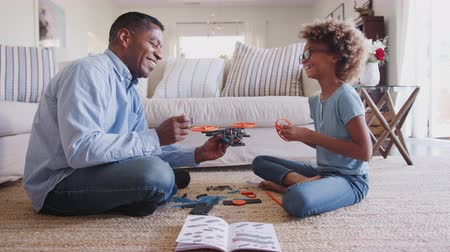 pré adolescente : Pre-teen girl and grandad sitting on the floor constructing a toy, looking at each other, side view