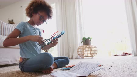 sitting floor : Pre-teen African American girl sitting on the floor building a construction kit toy, close up, full length