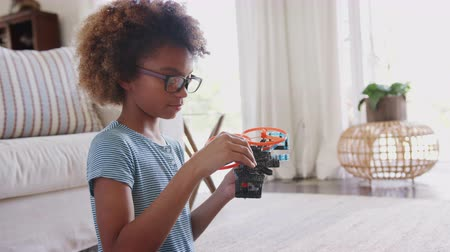 focus on foreground : Pre-teen African American girl sitting on the floor building a construction kit toy, close up, waist up