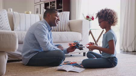 trois : Pre-teen girl and grandad sitting on the floor in living room building a model robot, side view