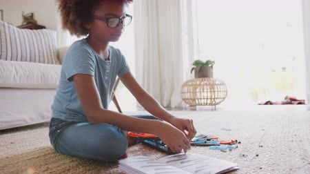 constructing : Pre-teen African American girl sitting on the floor in the living room building a construction toy, full length