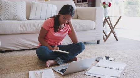 schoolbook : Teenage African American girl sitting on floor in the living room with laptop doing her homework, close up
