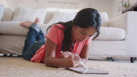 baixo ângulo : Teenage girl lying on the floor doing using a tablet computer and stylus, low angle, close up