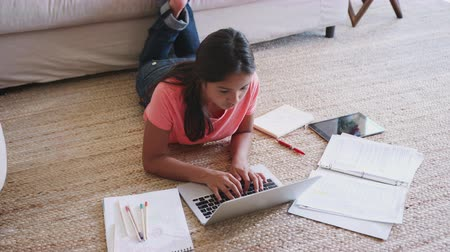 schoolbook : Teenage girl lying on the floor doing her homework using a laptop computer, elevated view, close up