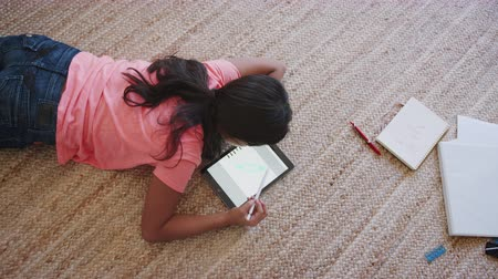 ped : Teenage girl lying on the floor in the living room using a tablet computer and stylus, overhead view